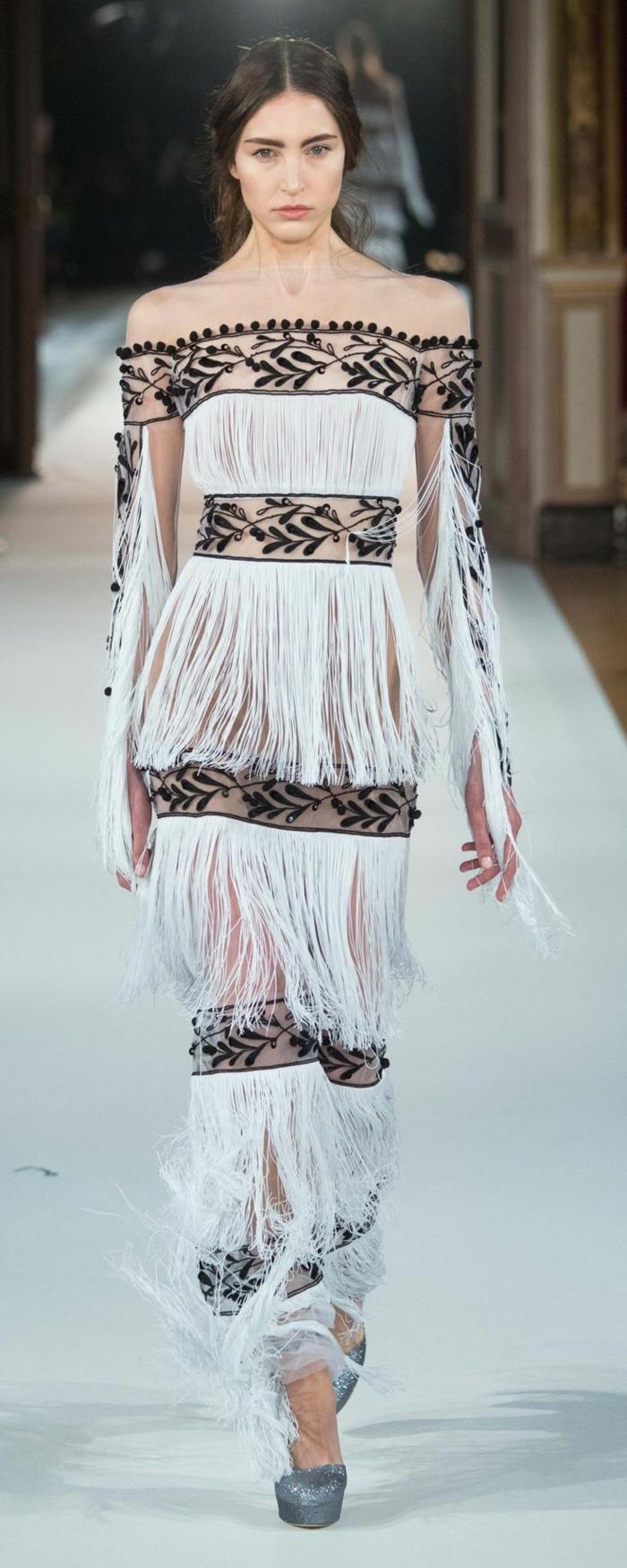 schwarz-weißes schlterfreies Kleid aus Troddeln und Spitze, schwarze Spitze mit Blättermotiven und Kristallen, Kleid ohne Ärmel, getragen mit silbernen Plattformschuhen mit Glitzer
