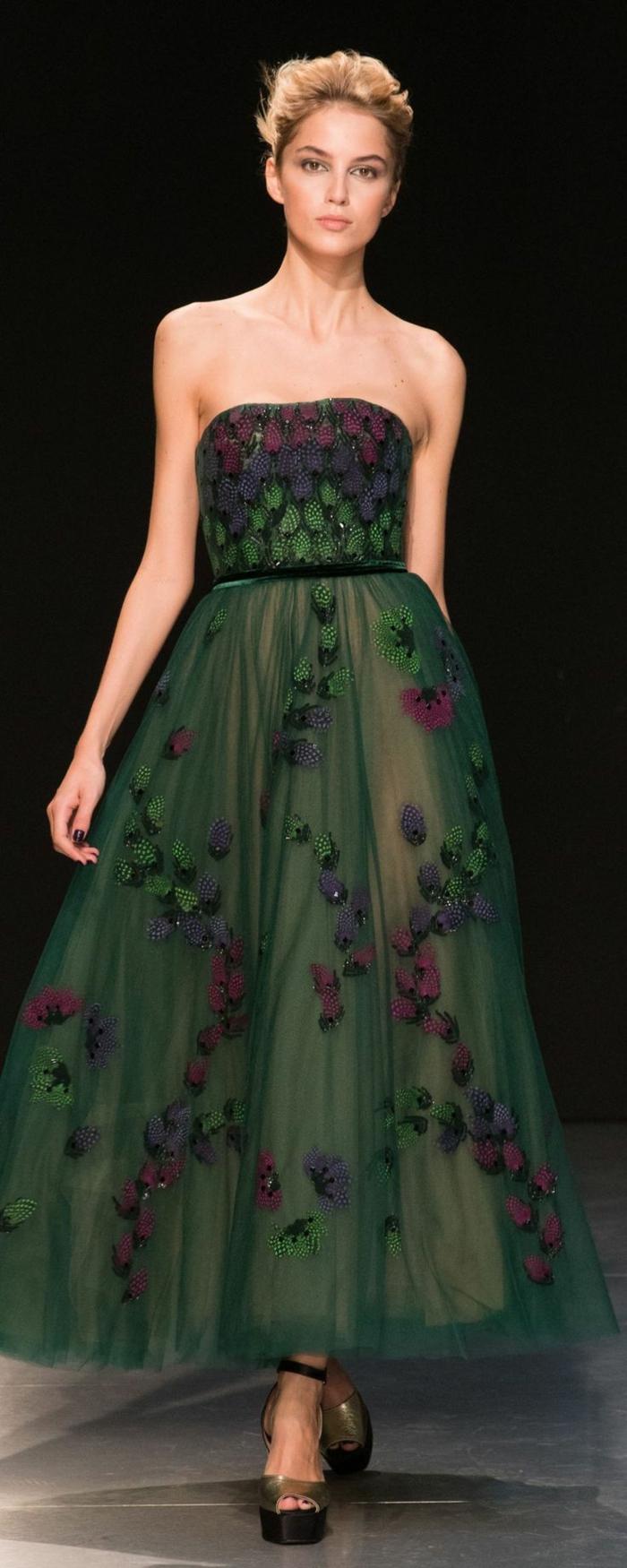 langes dunkelgrünes schulterfreies Kleid mit schmalem schwarzen Gürtel und vielen blauen, lila und grünen Applizierungen, kombiniert mit Plattformsandalen in Goldfarbe