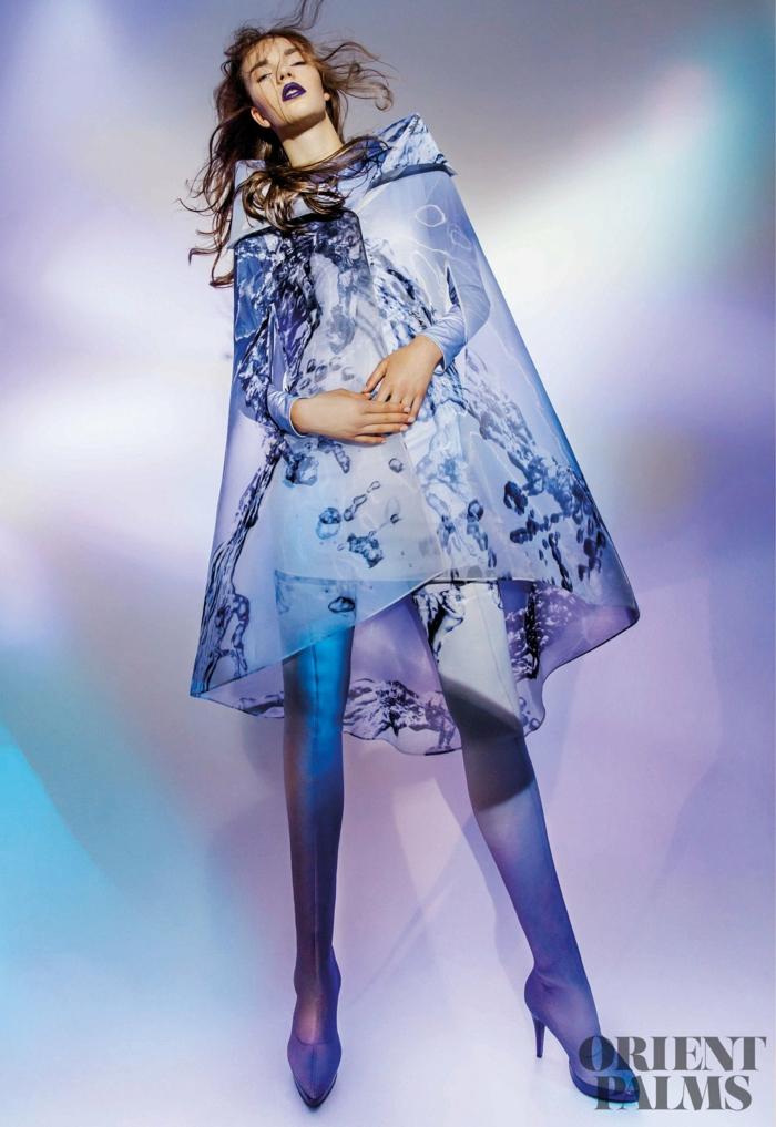 blauer Kleid-Umhang mit Print und Kapuze, silberne Strumpfhose mit einem Streifen, silberne Absatzscuhe mit kleinem Plattform, lässige lockige freifallende Haare