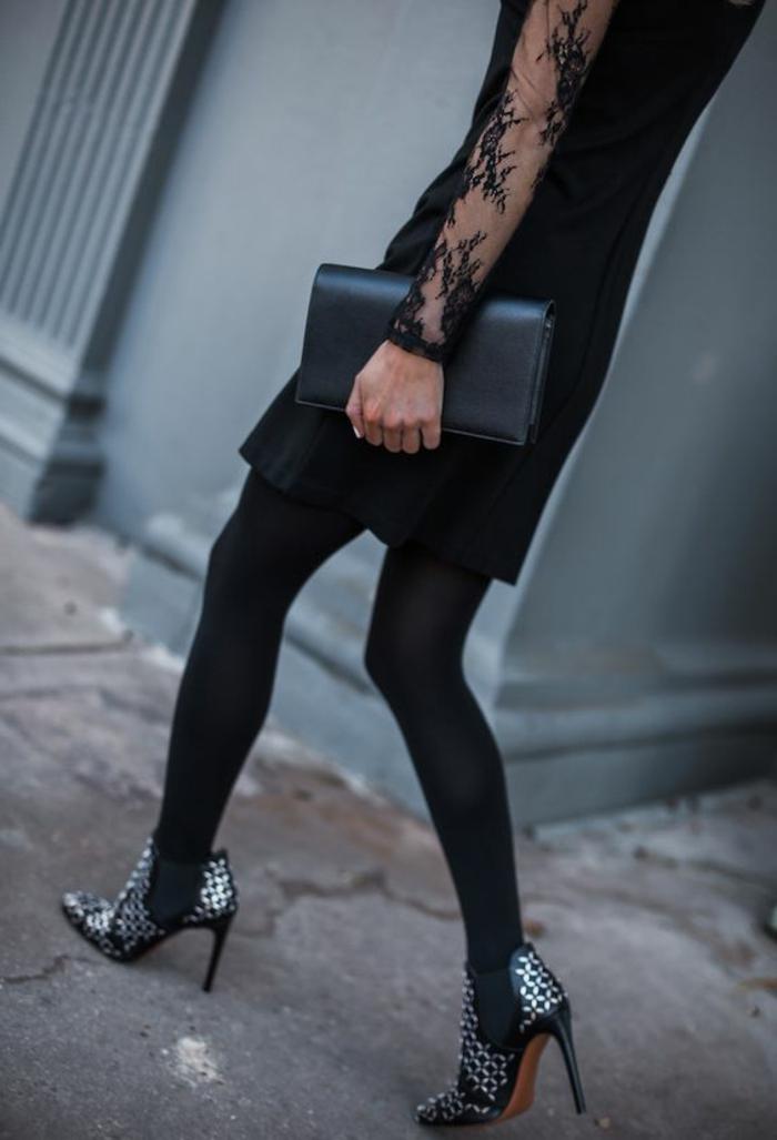 schwarzes Kleid mit mittlerer Länge mit feinem Design, Tüllärmel mit Applizierungen, schwarze Handtasche aus Leder, schwarze Winterstiefel mit Metallkapseln