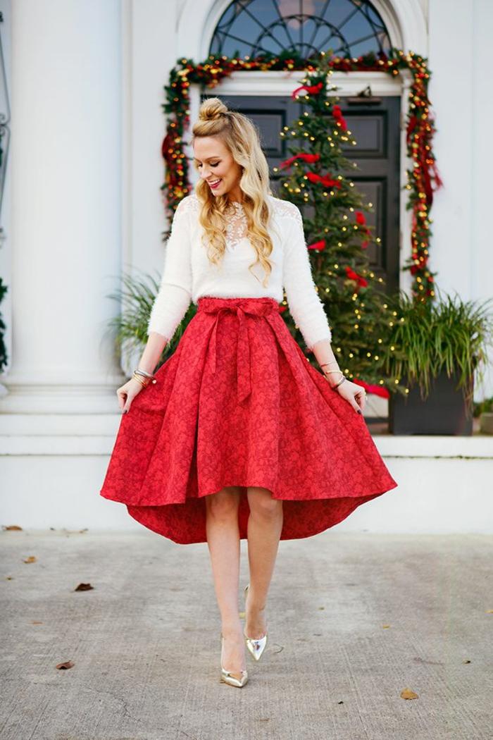 weißer Plüschpullover mit Spitze an den Schultern und ein roter Kleid mit Print und einer eleganten Schleife, kombiniert mit silbernen Lackschuhe, blonde lockige Haare mit Halb-Dutt, Hauseingang mit reichem Weihnachtsdeko
