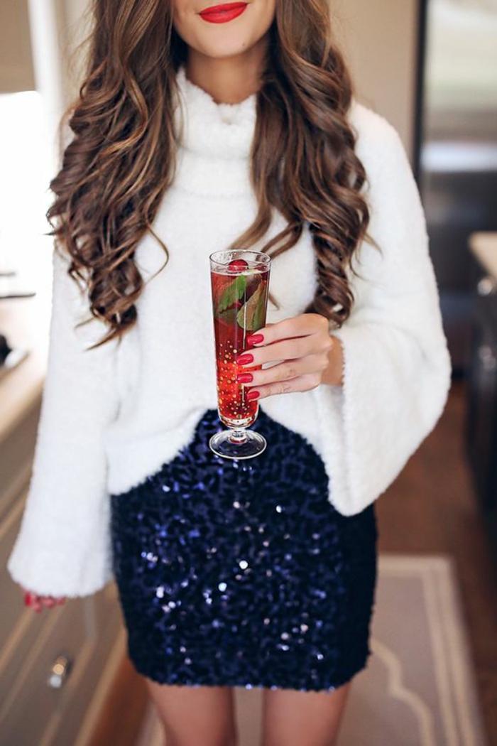 blauer Pailletten-Rock lang bis zum Knie, kombiniert mit einem weißen Plüschpulli mit Pollokragen und breiten Ärmeln, lange Nägel mit rotem Nagellack, braune Haare mit blonden Strähnen, Cocktail aus Erdbeeren