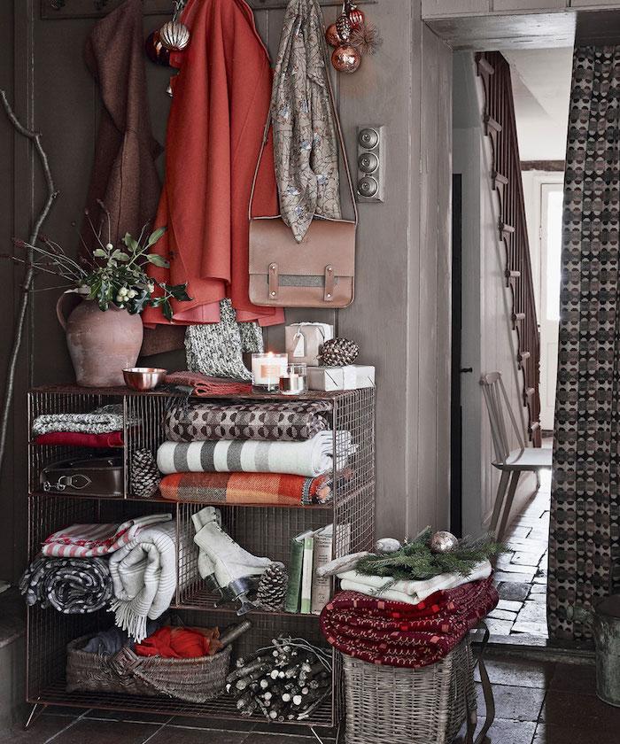 grau-lila Wand mit einem Mantelhänger, an der ein roter Mantel, eine dunkle Lederjacke und ein Schal in silberner Farbe hängen, kleine braune Ledertasche mit langem Henkel und grauer Applizierung, Keramik-Topf mit frischer Pflanze, Metallregal mit vielen Dekoartikeln darauf, viele Schlafdecken mit Prints, Weihnachtsdeko aus Weihnachtskugeln und dekorativen Zapfen, zwei Flechtkörbe, grüne Nadelbaumzweige mit einem Weihnachtskugel