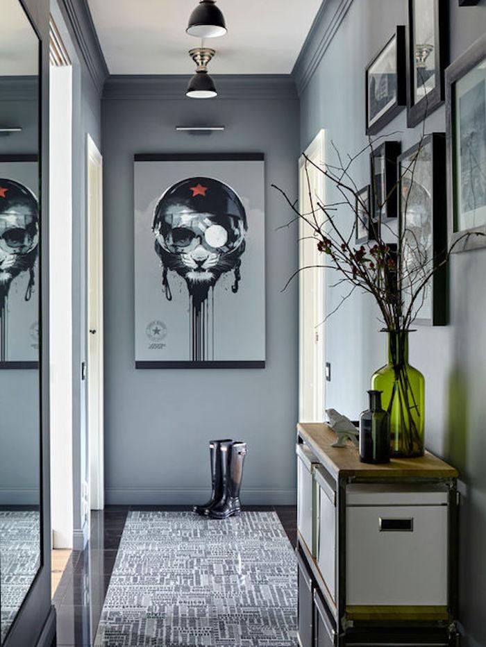 Flur grau gestalten, viele umrahmte Bilder an der Wand, Vase aus grünem Glas, Ikebana-Deko im Hauseingang, große weiße Aufbewahrungskisten aus Ikea, Film-Poster mit einer schwarzen Katze mit schwarzer Sonnenbrille und einem schwarzen Helm mit einem roten Stern in der Mitte, Winterstiefel aus schwarzem und braunem Leder, Tisch aus Holz und Metall, Teppich mit Labyrinth-Motiv, drei Zimmer mit offenen Türen