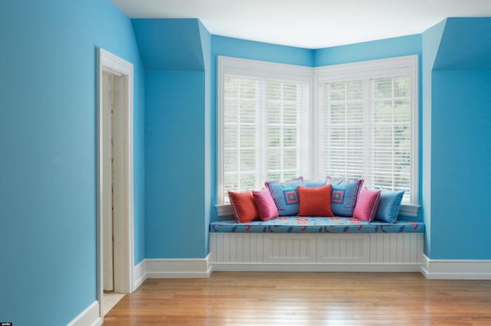 Innenflur mit großem Eckfenster, Innenflur mit blauen Wänden und weißer Decke, Eckfenster mit gemütlicher Leseecke mit vielen Kissen in verschiedenen Farben, Holzcouch mit Schubladen mit Schiebetüren, Schublade mit zweiflügeliger Tür, Holzcouch mit blauer Polstersitz, Zimmer mit weißer Tür, Haus mit Parkettboden