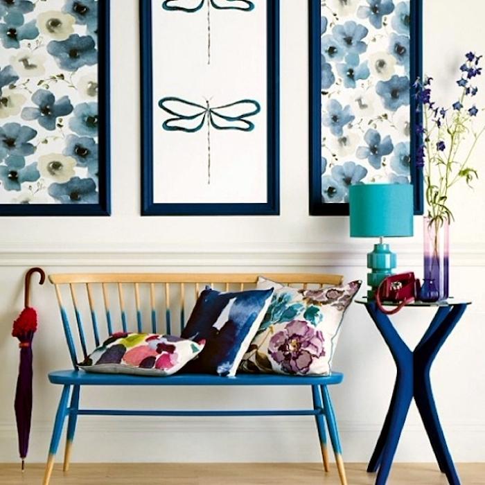 Korridor mit einer Sitzbank, gestrichen in zwei Farben - blau und beige, drei Deko-Kissen jeweils mit einem Blumen und zwei Punktemustern, kleiner Beistelltisch aus Glas und Holz mit langen dunkelblauen gekreuzten Beinen, Designer-Leselampe in Türkisblau, altes rotes Telefon mit Telefonscheibe, Vase aus farbigem Glas mit lila Blumen, drei Wandbilder in blauen Tönen, roter Regenschirm mit Holzgriff, weiße Wand mit einem weißen Wandsims