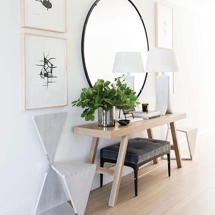 XXL Spiegel in runder Form mit schmalem schwarzen Rahmen, weiße Designer-Leselampe, Holztisch mit vier Beinen, dekoriert mit frischen grünen Pflanzen in einem Metalltopf, Wandbilder mit schwarzen Figuren, umklappbare Holzstühle in grauer Farbe, grauer Polsterhocker mit schwarzen Beinen