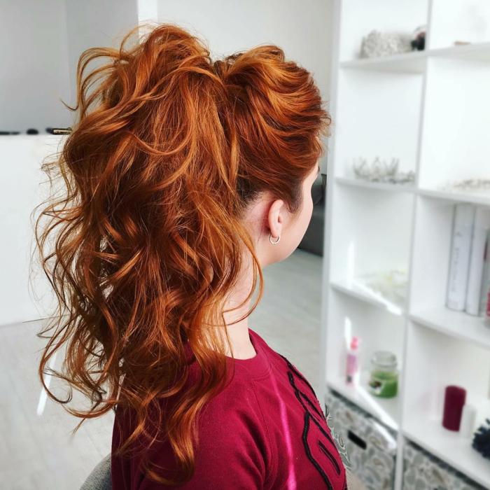 Frisuren für dünnes Haar - toupiertes Haar, gebunden zu einem hohen Pferdeschwanz, Haare mit Lickenstab leicht wellen, lange Haare mit Kupferfarbe, Friseursalon mit einem weißen Regal mit verschiedenen Styling-Produkten und Aufbewahrungsboxen, weinrotes TßShirt mit schwarzem Print