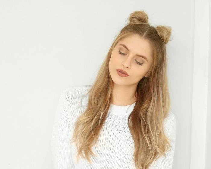 Frisuren für dünnes Haar, fines Haar stylen, zwei Halb-Dutts oben am Kopf, zwei Half-Buns hinten am Kopf, lange dunkelblonde Haare mit Platin-Strähnen, Frisur mit Mittelscheitel, dicke Lippen mit braunem Lippenstift, leichte Tagesschminke, Augenbrauen mit braunem Augenbrauen-Schminke, Mädchen mit gelber Hautunterton, Mädchen mit geschlossenen Augen trägt einen weißen Strickpulli