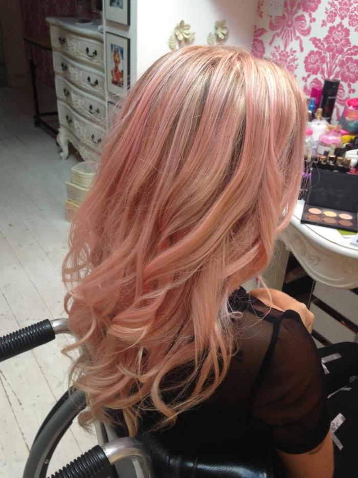 blondes dünnes Haar mit schwarzem Ansatz und rosa Strähnen, große Locken für mehr Volumen und einen lässigeren Look, schwarze halbdurchsichtige Bluse, weißer Schminktisch im Vintage-Stil, weiße Kommode im Vintage-Style, drei Aufbewahrungskister auf dem weißen Holzboden, Mustertapete mit pinken Blumen ,ein Schmink-Kasten auf dem weißen Tisch, vieele Haar- und Nägelprodukte wie Haarsprays und Nagellacks, Frau in einem Rollstuhl