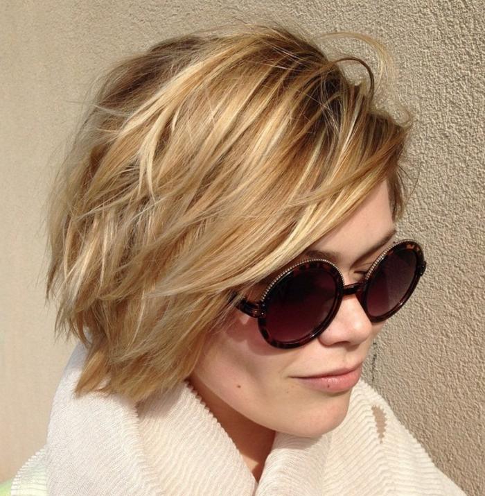 Frisuren für dünnes Haar - strukturierte Haare mit blonden Strähnen, Seitenpony-Frisur mit Seitenscheitel, Designer-Sonnenbrille mit runder Form, lila Gläsern und Leoparden-Rahmen, weißer Pulli mut hohem Kragen, Frau mit einem Muttermal an der rechten Wange