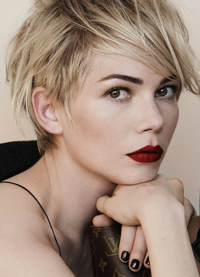 moderene Frisur für kurze Haare, gestylt mit Haarlack, weizenblonde strukturierte Haare mit dunklem Ansatz, Fotomodell mit dunkelgrünen Augen, Stupsnase und dicken roten Lippen