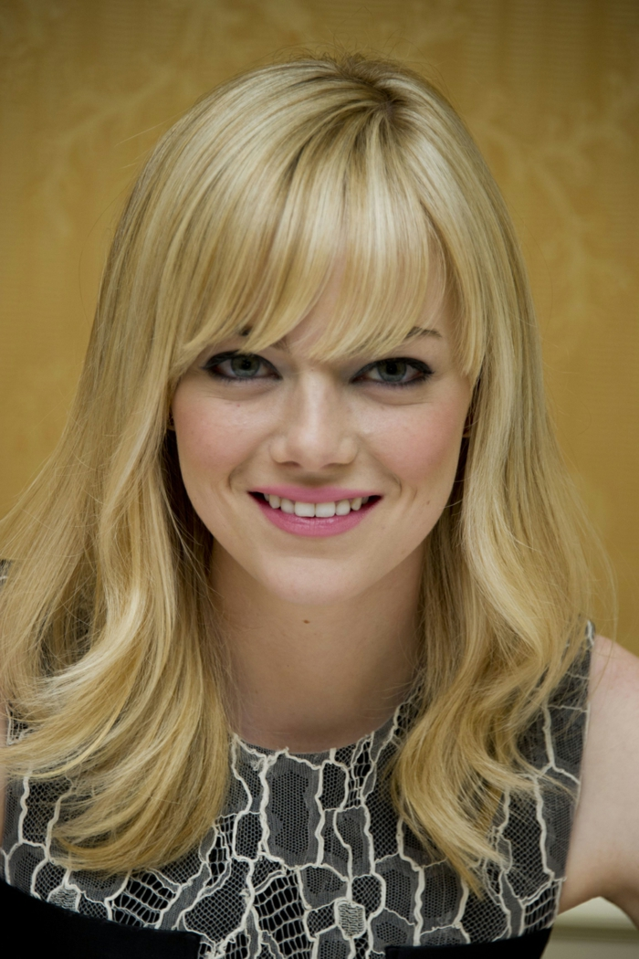 Hollywood-Star mit blondem Haar, Ponyfrisur mit Seitenscheitel, leicht gewellte Spitzen, rosa Lippenstift und schwarzer Augenstift, hellblaue Augen mit Mandelforn, graues Kleid mit Schlangen-Print