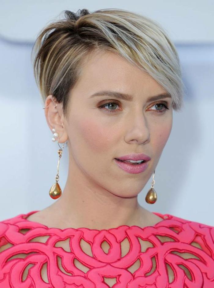 Kurzhaarfrisuren für dünnes Haar - Scarlett Johansson mit kurzen Haaren in zwei Farben, kurzer Haarschnitt mit Seitenpony - auf der rechten Seite sind die Haare kürzer und nach hinten gestylt, auf der linken Seite sind sie länger und nach vorne gestylt, Scarlett Johansson trägt braune Lidschatten und ein Designer-Kleid in Rofarbe mit vielen Löchern, Ohrringe aus weißen Perlen und große Goldorringe