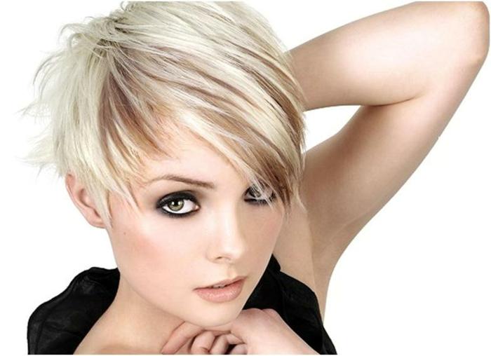 90s Look - strukturierter kurzer Haarschnitt mit Seitenpony, weißblonde Haare mit braunen Strähnen, dünn gezupften Augenbrauen, schwarzer Eyeliner und orangenfarbenes Rouge, große grüne Augen