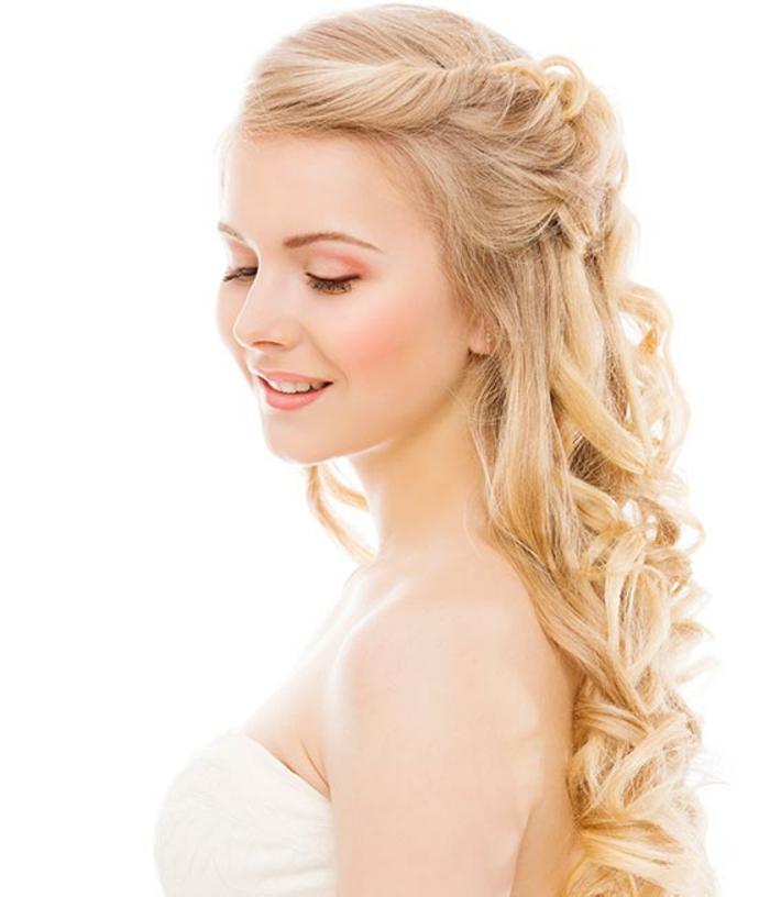 blondes lockiges Haar mit Twist, Frisur mit Seiten-Twist, rosa Schminke mit schwarzem Ezeliner, kleine weiße Zähne, weißes Kleid schulterfrei, Hochzeitskleid ohne Träger