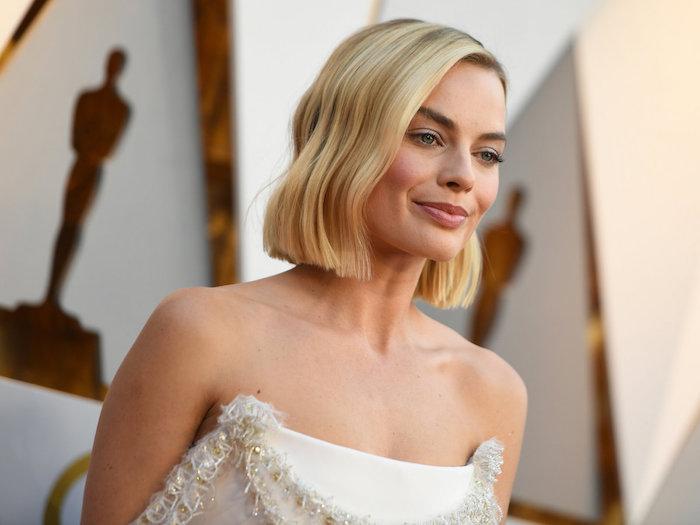 Kurzer Bob Haarschnitt, gewellte blonde Haare mit Seitenscheitel, weißes trägerloses Abendkleid