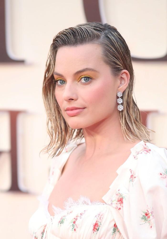 Wet Look Haare, seitlich getragen, weißes Kleid mit Blumenmuster, gelber Lidschatten und matter Lippenstift, silberne Ohrringe mit Kristallen