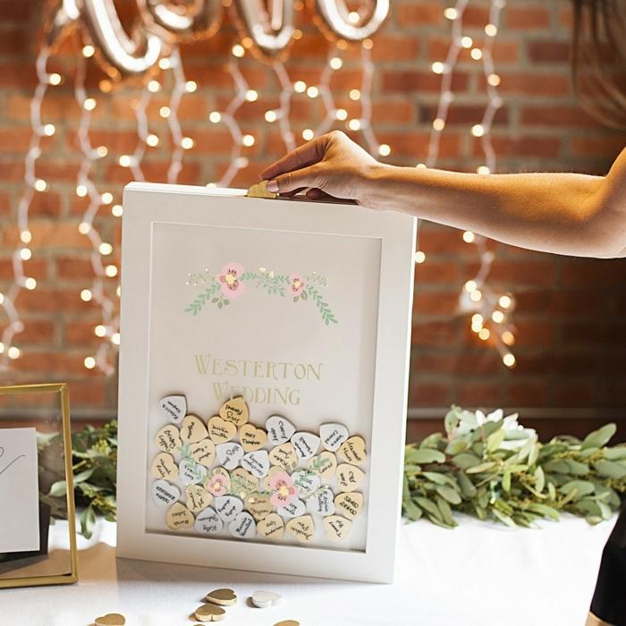 Den eigenen Namen oder Glückwunsch auf kleines Holzherz schreiben, schöne Idee für Hochzeitsgästebuch