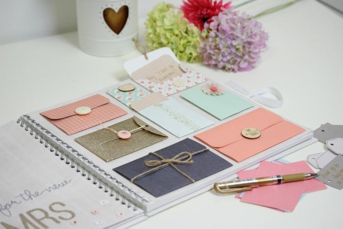 Schönes Hochzeitsgästebuch mit bunten Applikationen und Briefumschlägen, Blumen und Karten