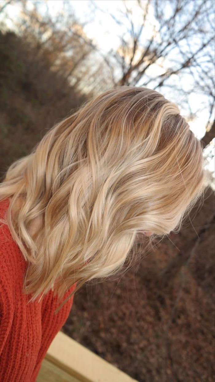 ein Mädchen mit rotem Pullover, schulterlange Haare, ein Etage Schnitt - hellbraune Haare