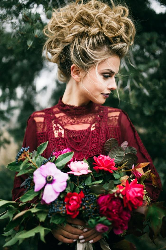 Hochsteckfrisur für dickes Haar, weinrotes Spitzenkleid mit langen Ärmeln, bunter Blumenstrauß