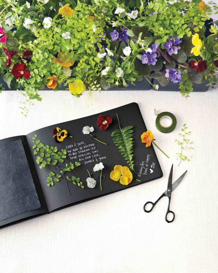Hochzeitsgästebuch mit Blüten und Blättern verziert, weiße Aufschriften auf schwarzem Grund