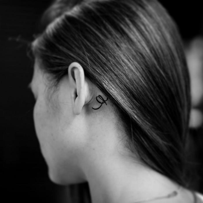 tattoo motive hinterm ohr - eine junge frau mit einem kleinen schwarzen tatttoo hinter ihrem ohr
