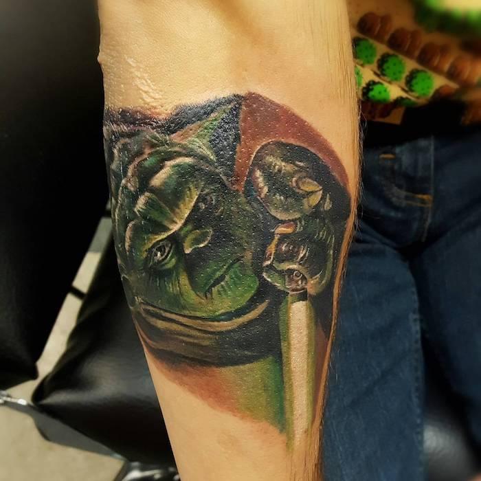 eine hand mit einem grünen kleinen jedi - joda mit seinem grünen lichtschwert