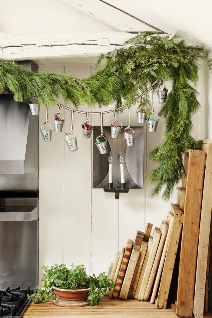 Girlande mit kleinen Eimern voll mit Geschenken und Süßigkeiten, Tannenzweige für Weihnachtsdekoration