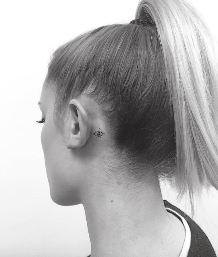 eine junge frau mit einem winzigen swchwarzen tattoo mit augen - tattoo