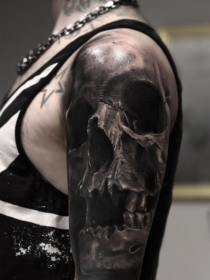 eine hand einer frau mit einem sternen tattoo und einem großen tattoo mit einem großen schwarzen totenkopf mit schwarzen augen und zähnen - totenkopf tattoo