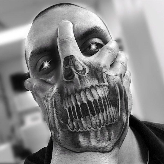 eine hand mit einem großen schwarzen tattoo mit einem schwarzen totenkopf mit weißen zähnen - mann mit totenkopf tattoo