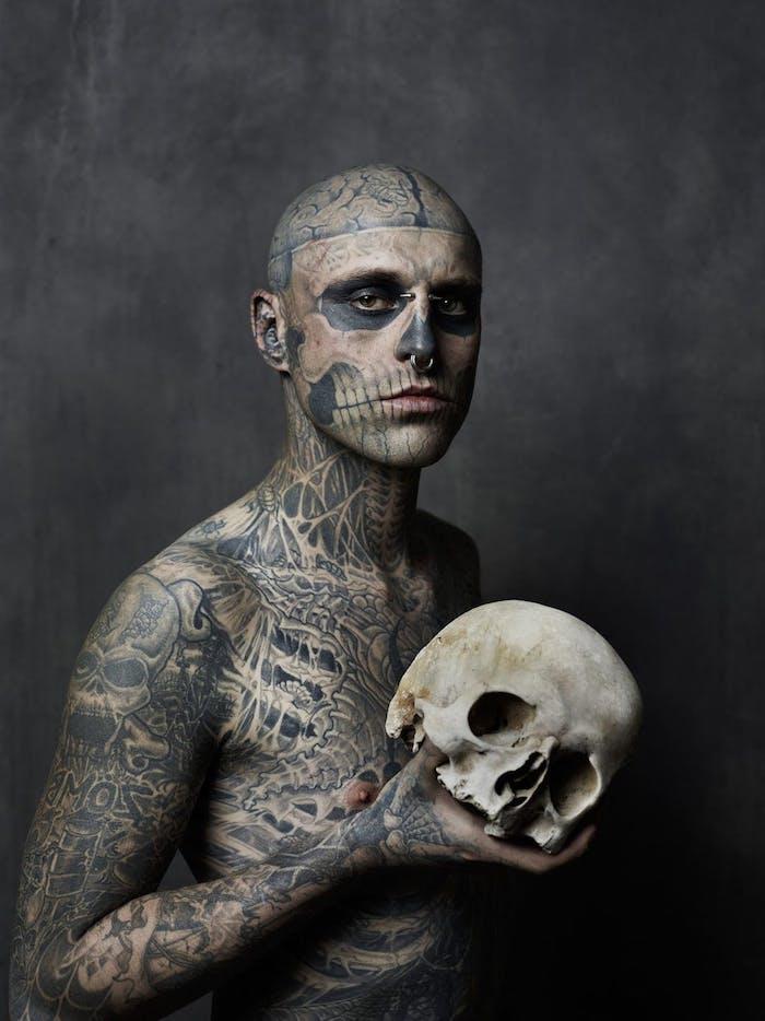 tattoo totenkopf - ein mann mit einem weißen großen totenkopf und mit vielen tätowierungen - ein tattoo mit einem großen weißen totenkopf mit schwarzen augen