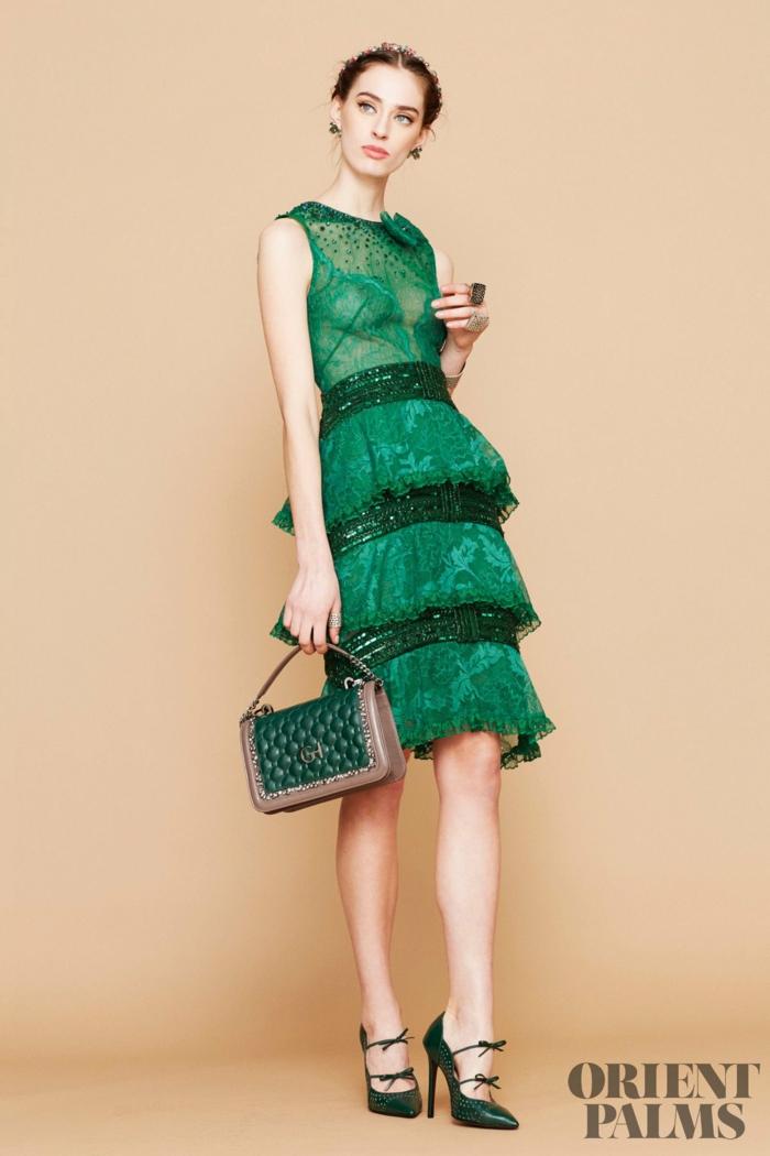 Grünes knielanges Spitzenkleid, mit Pailletten verziert, dunkelgrüne Handtasche und High Heels