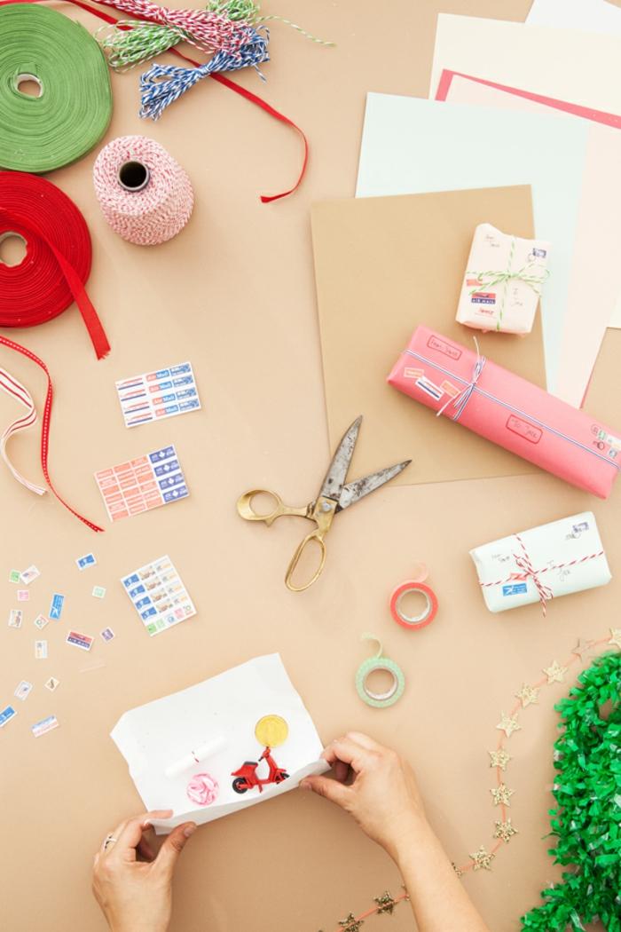 Adventskalender einfach und schnell selber machen, kleine Spielzeuge mit Papier verpacken und mit Faden verzieren
