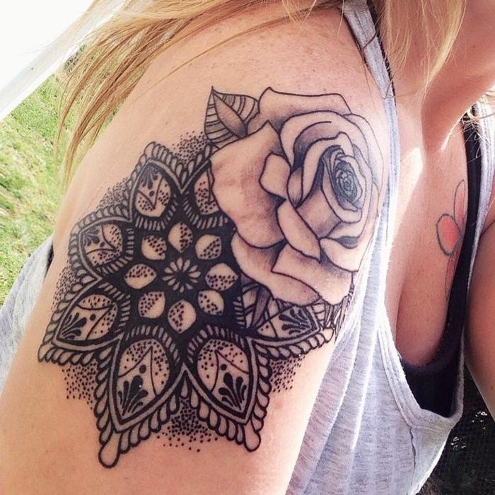 eine große graue Rose mit einem Blatt auf der linken Seite und ein schwarzes Mandala mit vielen schwarzen Punkten, tättowiert auf dem rechten Schulter einer Blondine mit golblonden Haaren, die ein schwarzes Oberteil trägt und ein Blumentattoo auf der linken Seite an der Brust hat