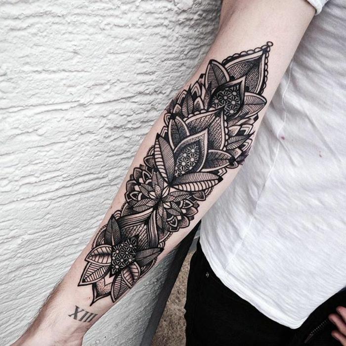 Frau mit schwarzem Unterarmtattoo auf dem rechten Arm, schwarzer Tattoo mit komplizierten Motiven, Blumen- und Blättermotive mit vielen Linien, Tattoo mit Datum, schwarze Hose mit weißem T-Shirt kombinieren