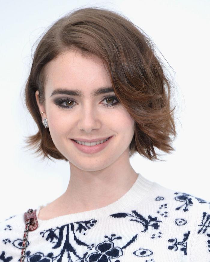 ein Mädchen mit kurzem braunem Haar hat einen weißen Pullover an, schönes Lächeln