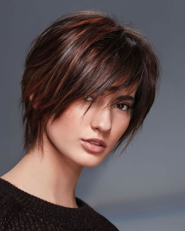 ein junges Mädchen mit braunem Haar mit roten Strähnchen, eine schwarze Bluse