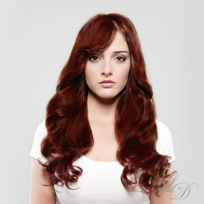 junges Mädchen mit länglichem Gesicht, Mund mit vollen Lippen, schönen großen braunen Augen, gerade Augenbraun und langes lebendiges Haar, gefärbt in Rotbraun mit Kupfernuancen, ihr Haar hat große Locken, die Frisur ist mit seitlichem Pony