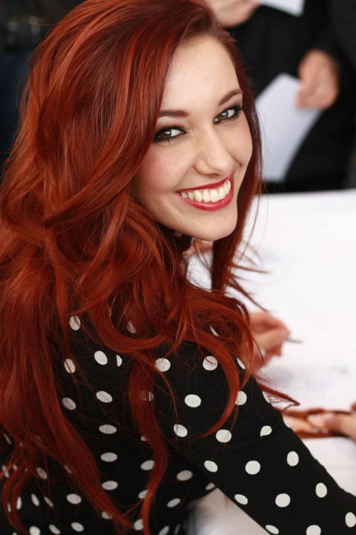 gut gepflegte rote Haare mit Kupfer-Strähnen, freifallende strukturierte Stähnen, Haar mit Seitenscheitel, großer Mund und große weiße Zähne, Mädchen mit einem breiten Lächeln auf dem Gesicht, schwarze Bluse mit langen Ärmeln mit Print von weißen Punkten