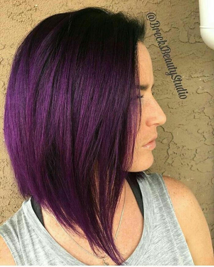 Bob-Frisur für mittellange glatte Haare, gefärbt in Lila, mittellanges Haar mit fast schwarzem Ansatz und lila Längen, graues Top mit dicken Trägern, Brusthalter mit schwarzen Trägern