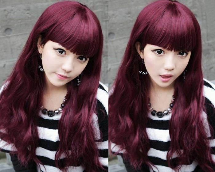 junges asiatisches Mädchen mit langen leicht gewellten Haaren mit Ponyfrisur, Frisur mit geradem Pon für lange gewellte Haare, Plüschpulli mit schwarzen und weißen Streifen, Halskette und Ohrringe aus Perlen