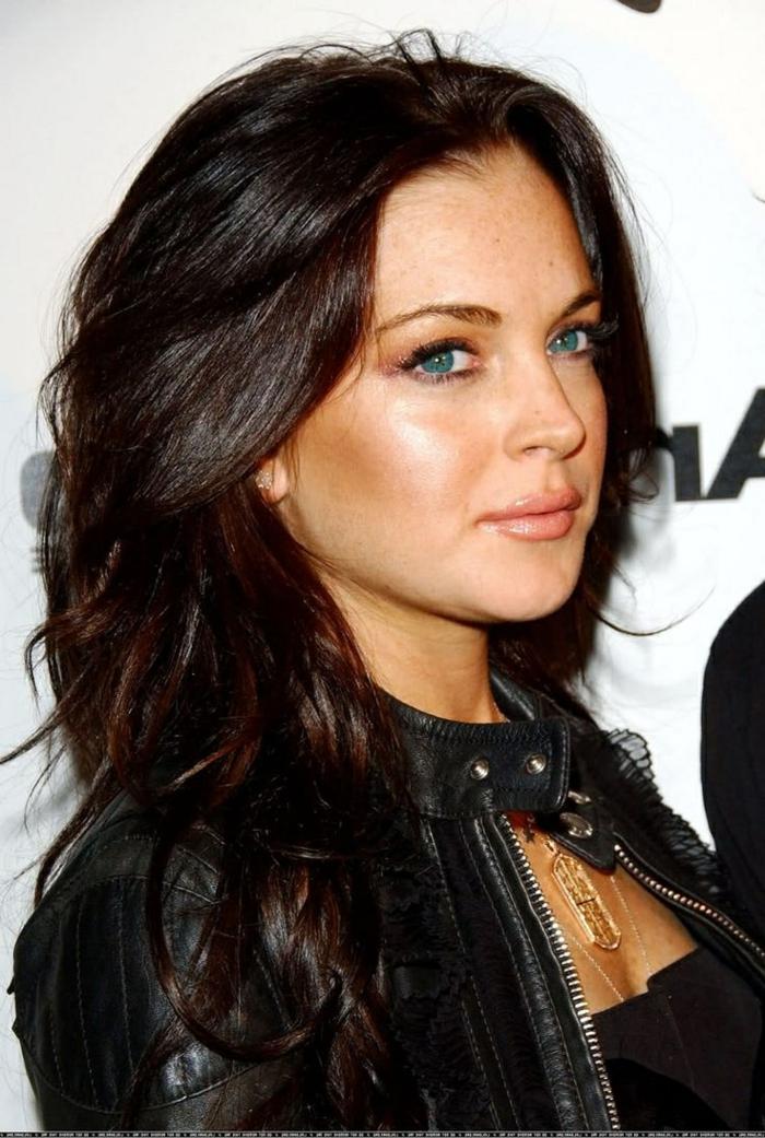 Lindsay Lohan mit schokoladenbraunen Haaren mit Glanzreflexen, Lindsay Lohan mit blauen Augen mit Gold-Schminke, schwarze Lederjacke mit kleinem geradem Kragen, vielen Plissees und Applizierungen mit Spitze, Halsschmuck aus Gold,goldener Halsschmucke-Stern, schwarzes Top schulterfrei