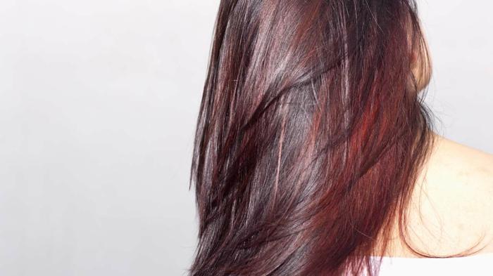 glänzende lebendige Haare mit dunklem Satz mit Mahagoni Farbschattierung und roten Reflekten auf den Längen, weiße Bluse-Schulterfrei, Bild mit leicht grauem Hintergrund