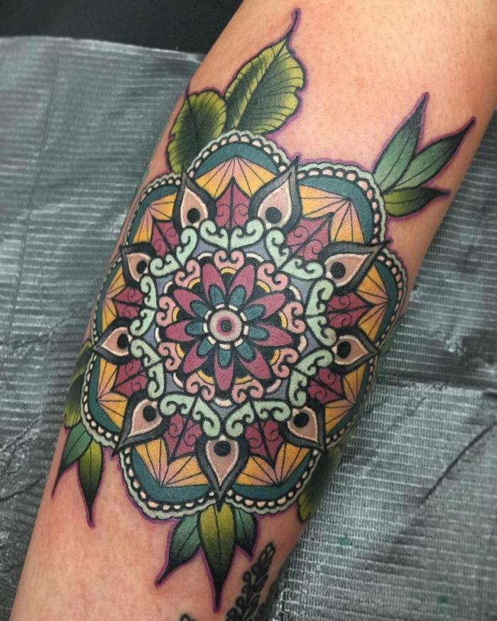 farbige Tätowierung mit vielen Ornamenten und vielen grünen Blättern, weißen Punkten und schwarzen Konturen