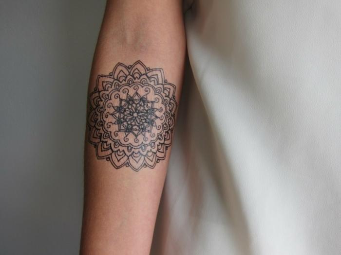 runder Tattoo Mandala mit vielen Ornamenten, eifarbiger Tattoo auf der inneren Seite des Armes einer Frau, gekleidet mit einer weißen Satinbluse