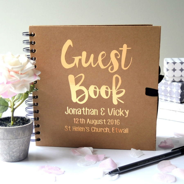 Hochzeitsgästebuch mit goldener Aufschrift, Namen der Braut und des Bräutigams, Hochzeitsdatum und Ort, weiße Rose in Blumentopf