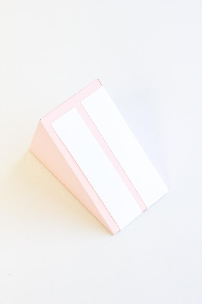 Schachteln falten - ein Stück Torte aus Papier, die weiße Streifen auf rosa Hintergrund